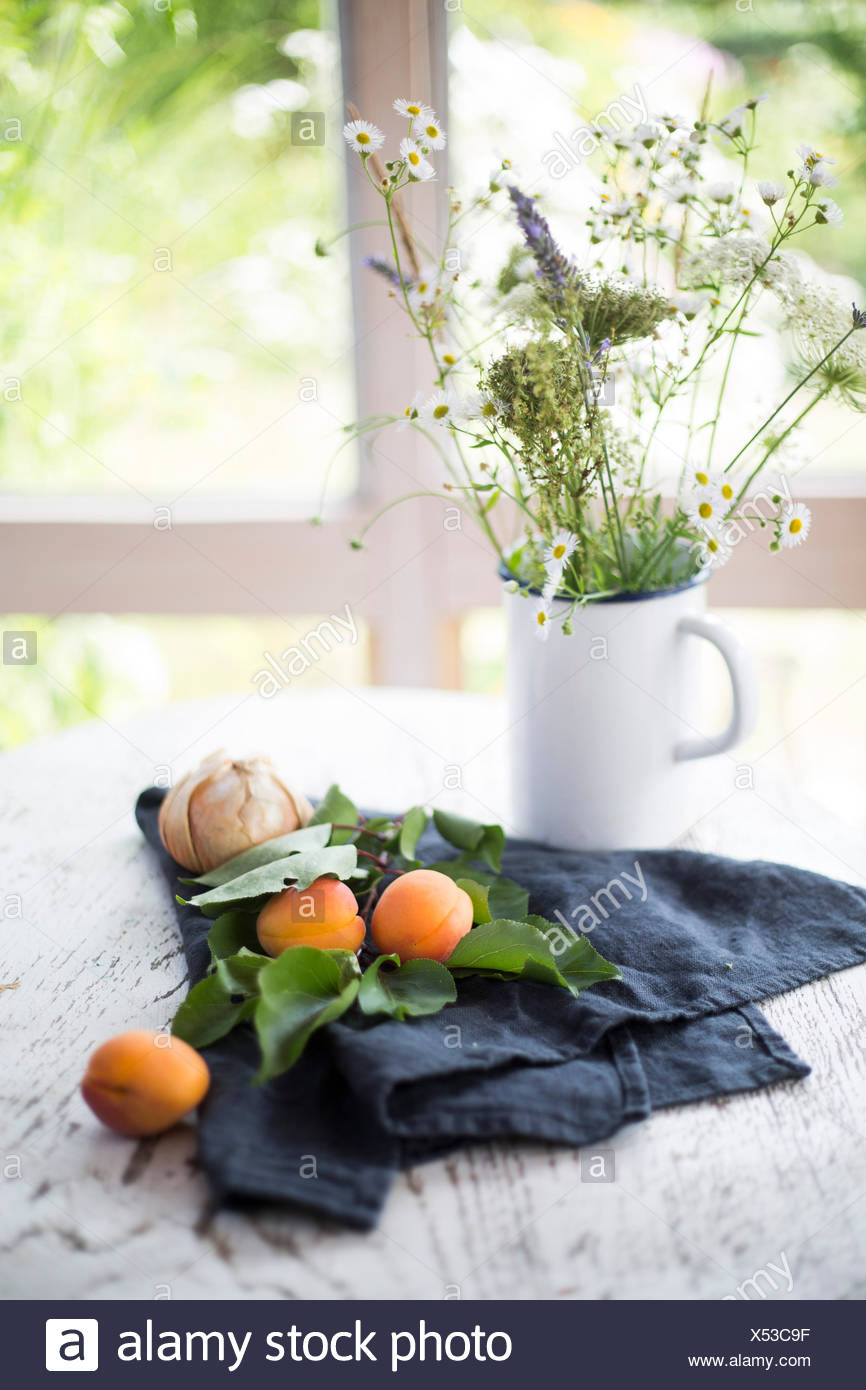 Apricots and onions with grey kitchen towel and flower bouquet on apricots and onions with grey kitchen towel and flower bouquet on white wooden table with garden view in the background izmirmasajfo