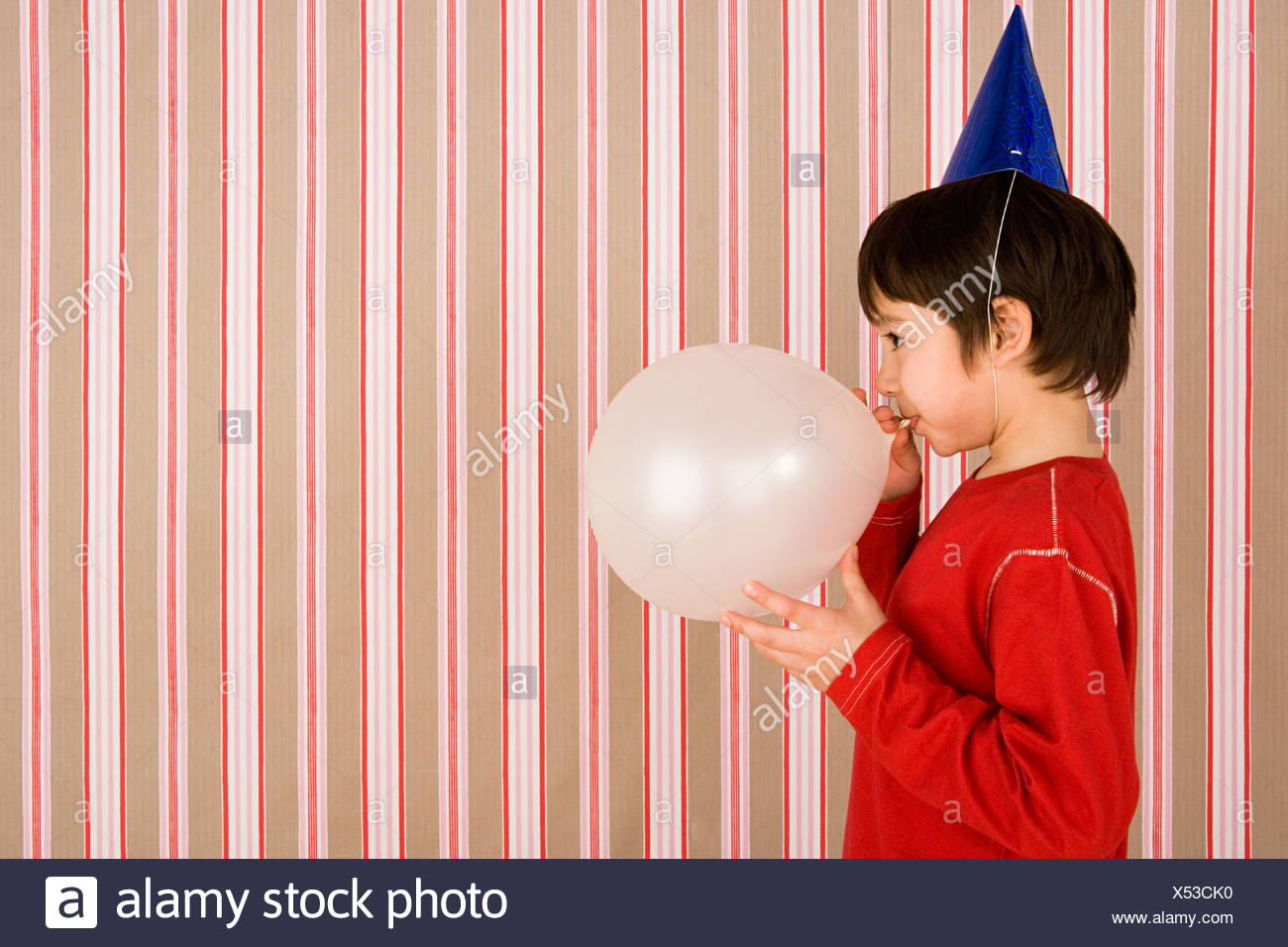 Boy blowing up balloon - Stock Image