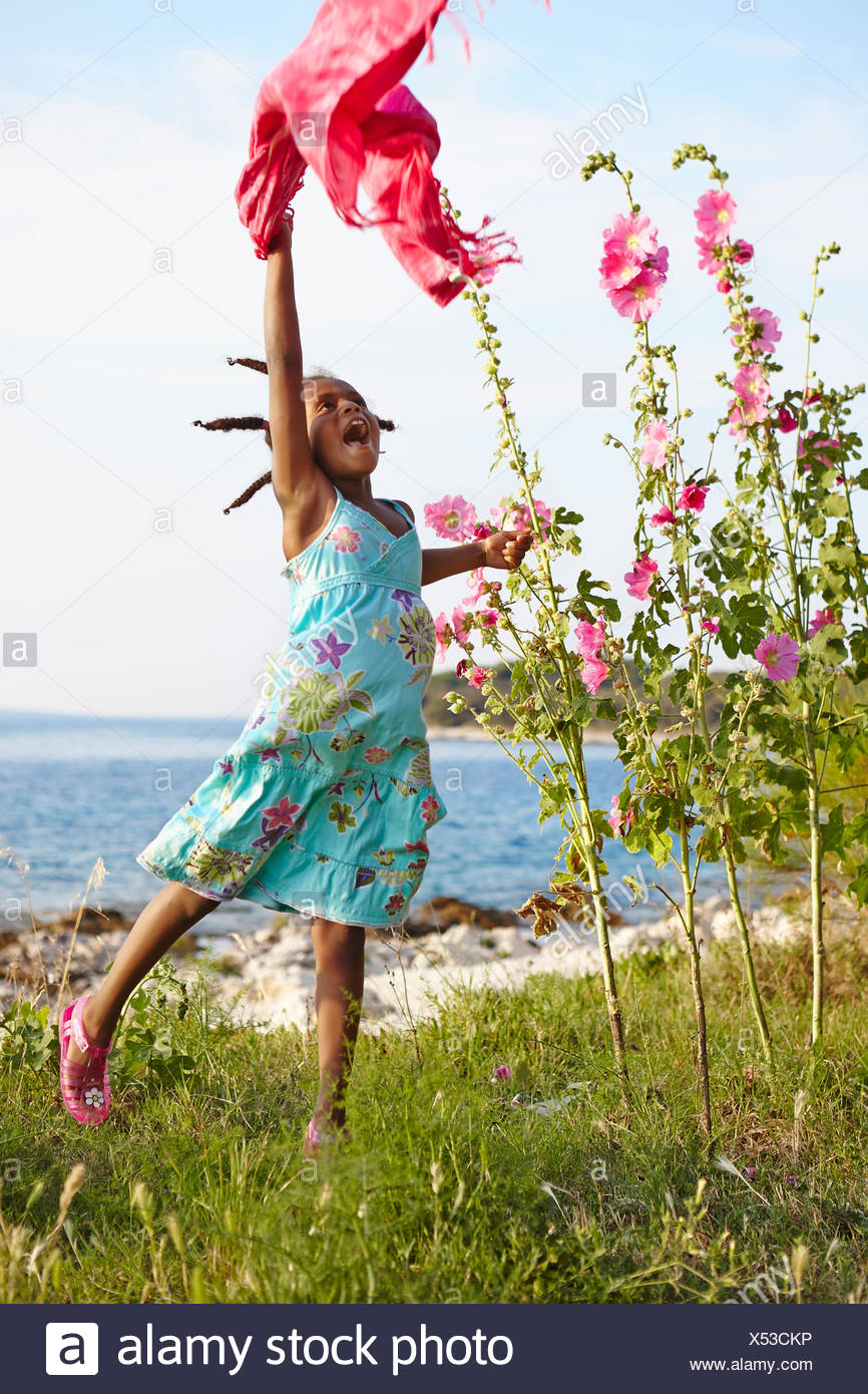 Croatia, Dalmatia, Silba, Girl (6-7) playing on sea coast - Stock Image