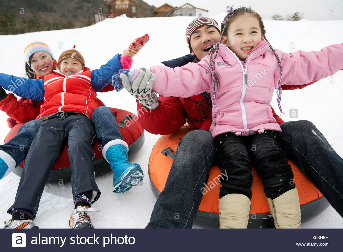 Parents And Children Riding On Inflatable Snow Tube Stock Photo