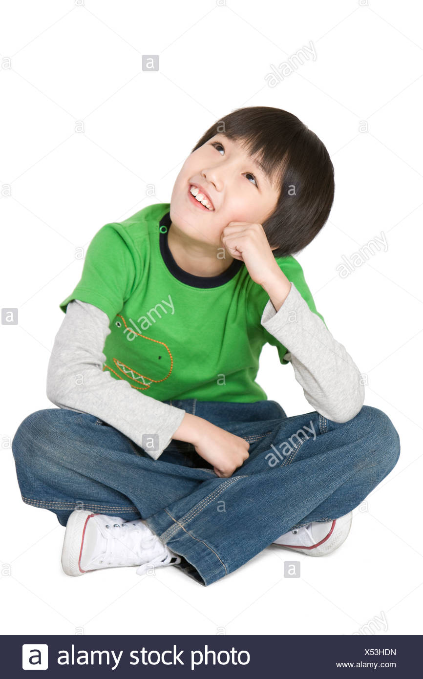 Young boy sitting and looking up thinking - Stock Image