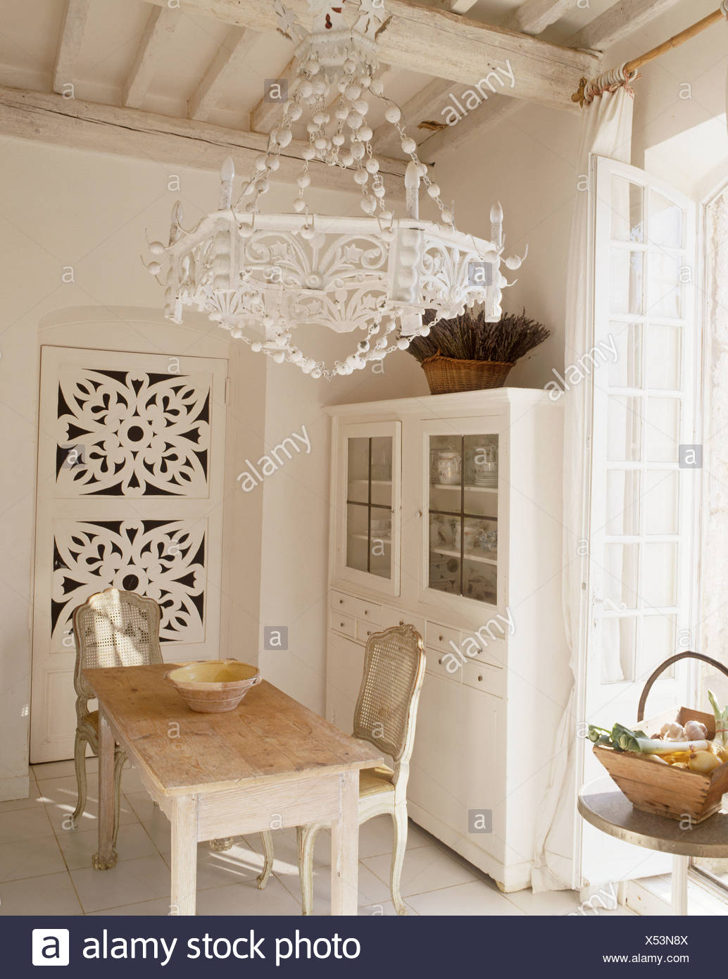 Ornate white light on white beamed ceiling above scrubbed ...