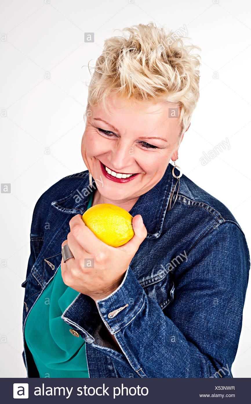 portrait of middelaged beautiful woman eating fresh lemon Stock Photo