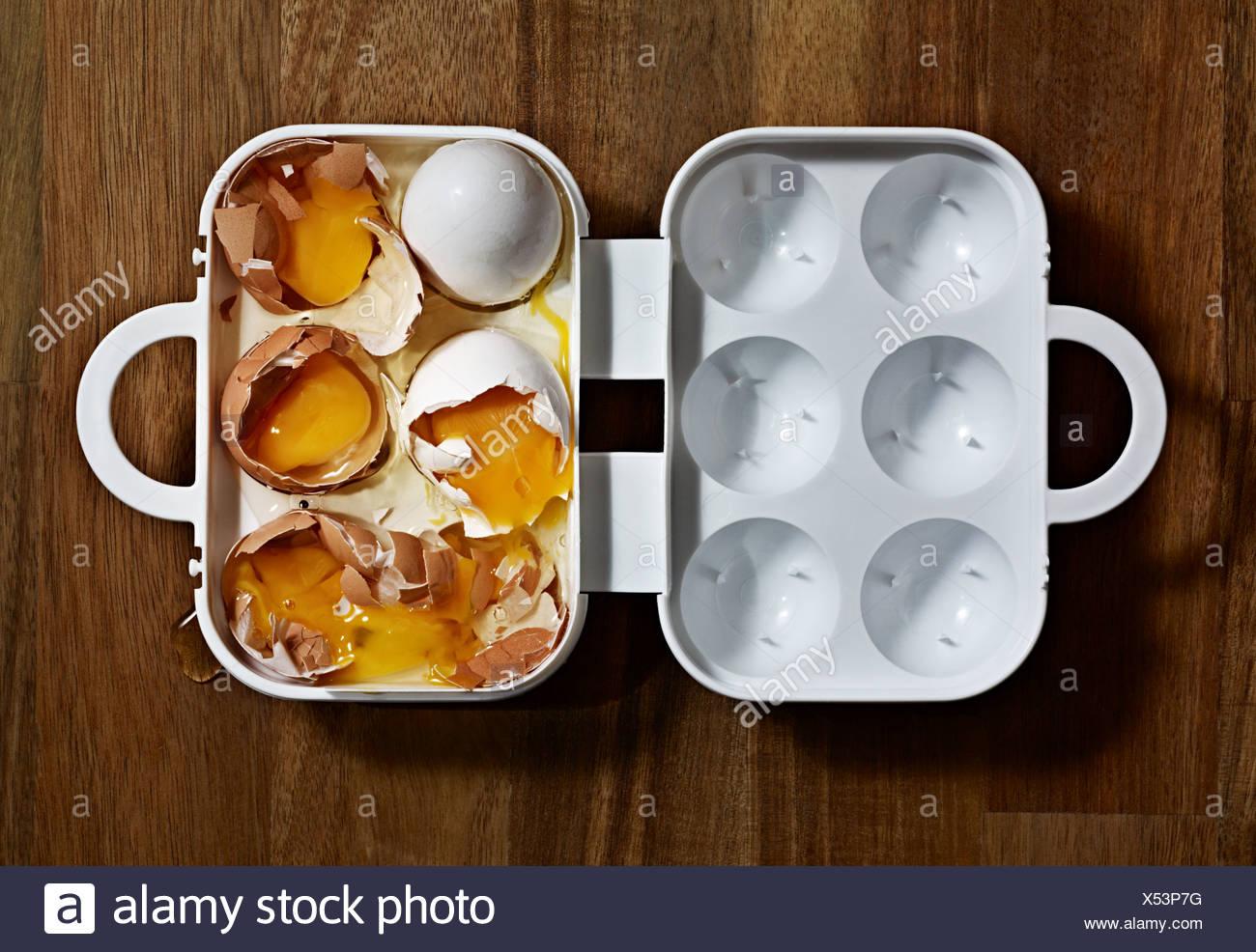 Broken eggs in a carton - Stock Image
