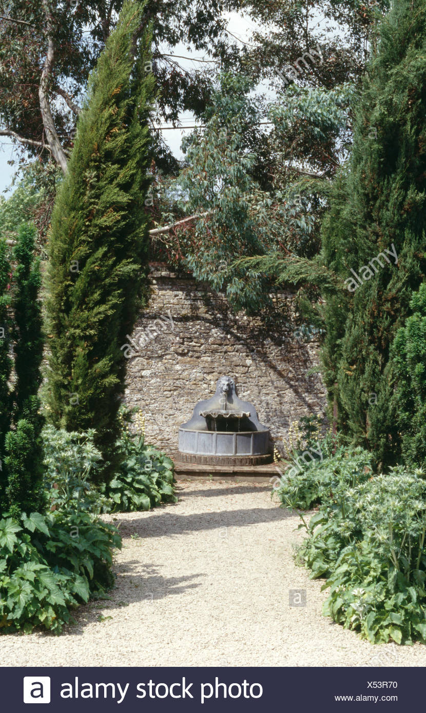 Conifers either side of gravel path to lead fountain in a large country garden - Stock Image