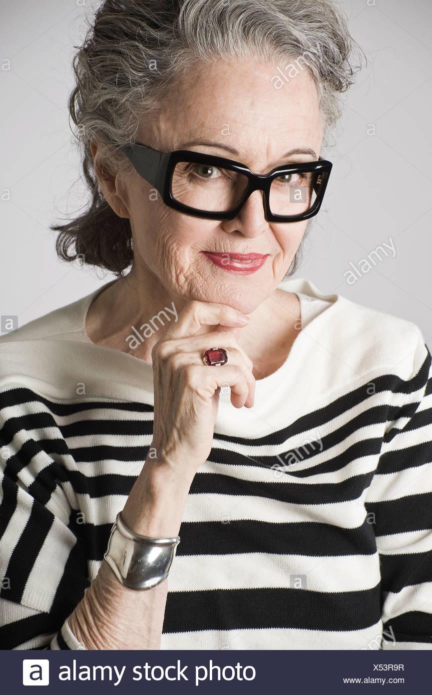 Portrait of senior woman, hand on chin - Stock Image