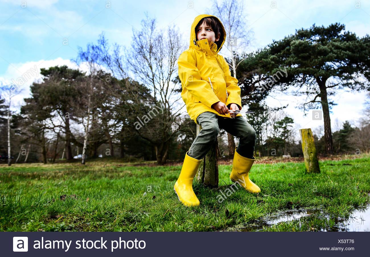 Boy in yellow anorak sitting on park fencepost - Stock Image