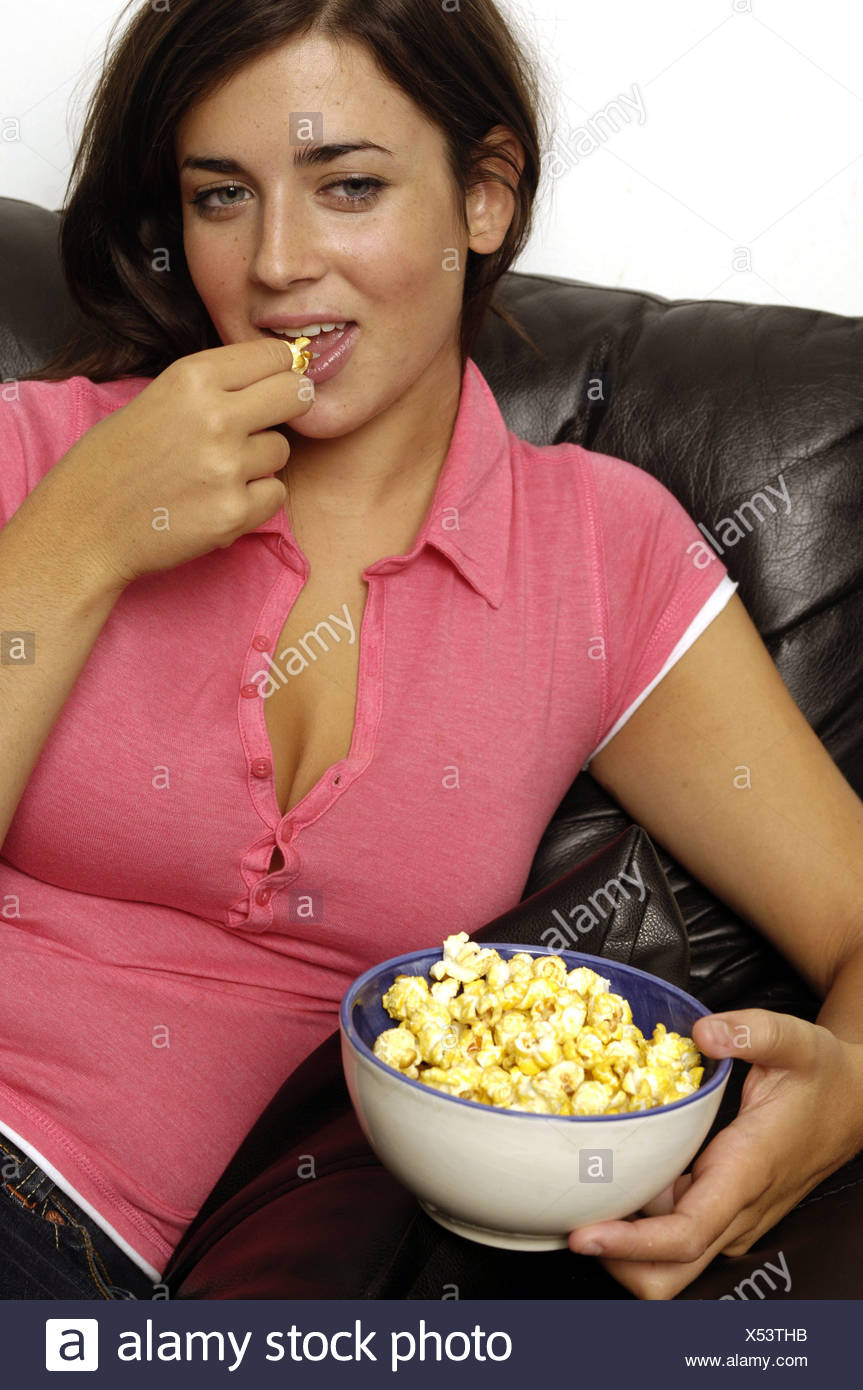 female with brunette hair wearing pink t shirt sitting on sofa