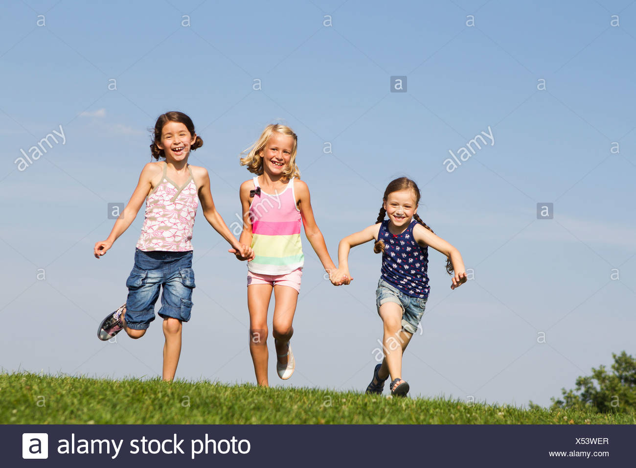 Girls running together in field - Stock Image