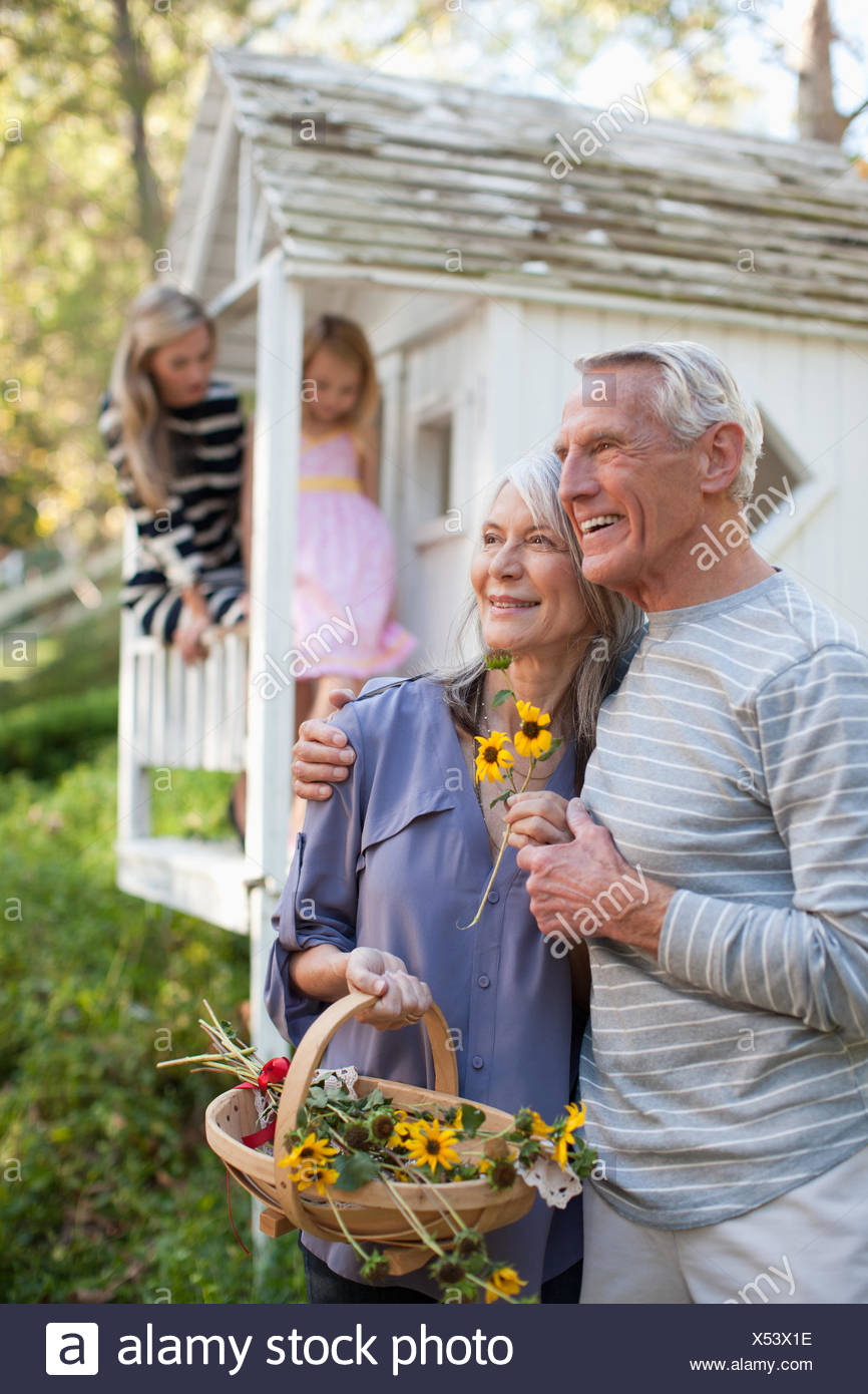 Older couple picking flowers outdoors - Stock Image