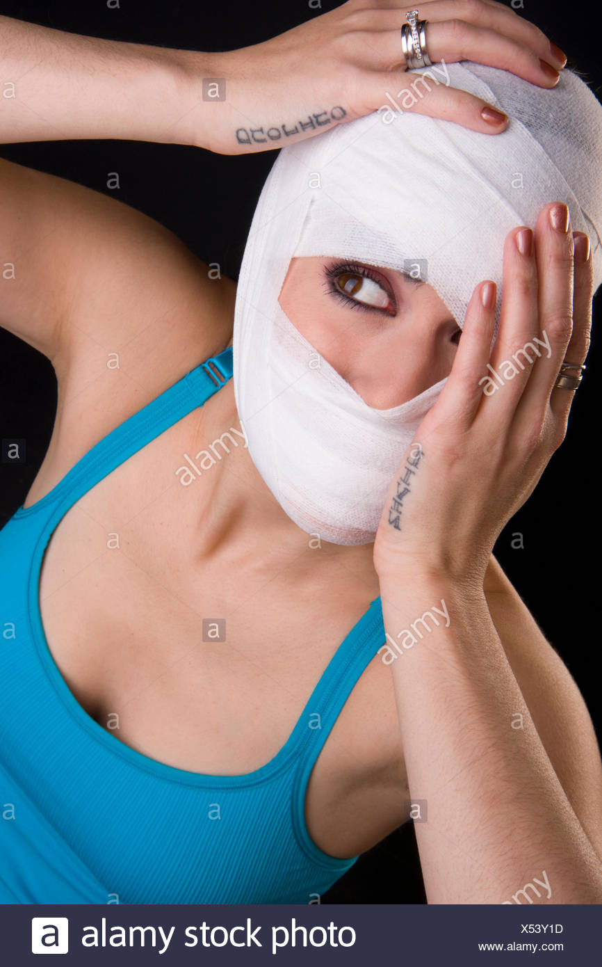 Female Holds Face First Aid Gauze Wrapped Head Injury Pain - Stock Image