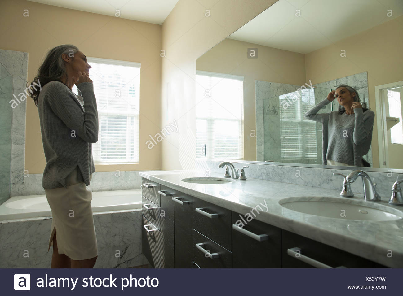 Woman pondering in front of mirror - Stock Image