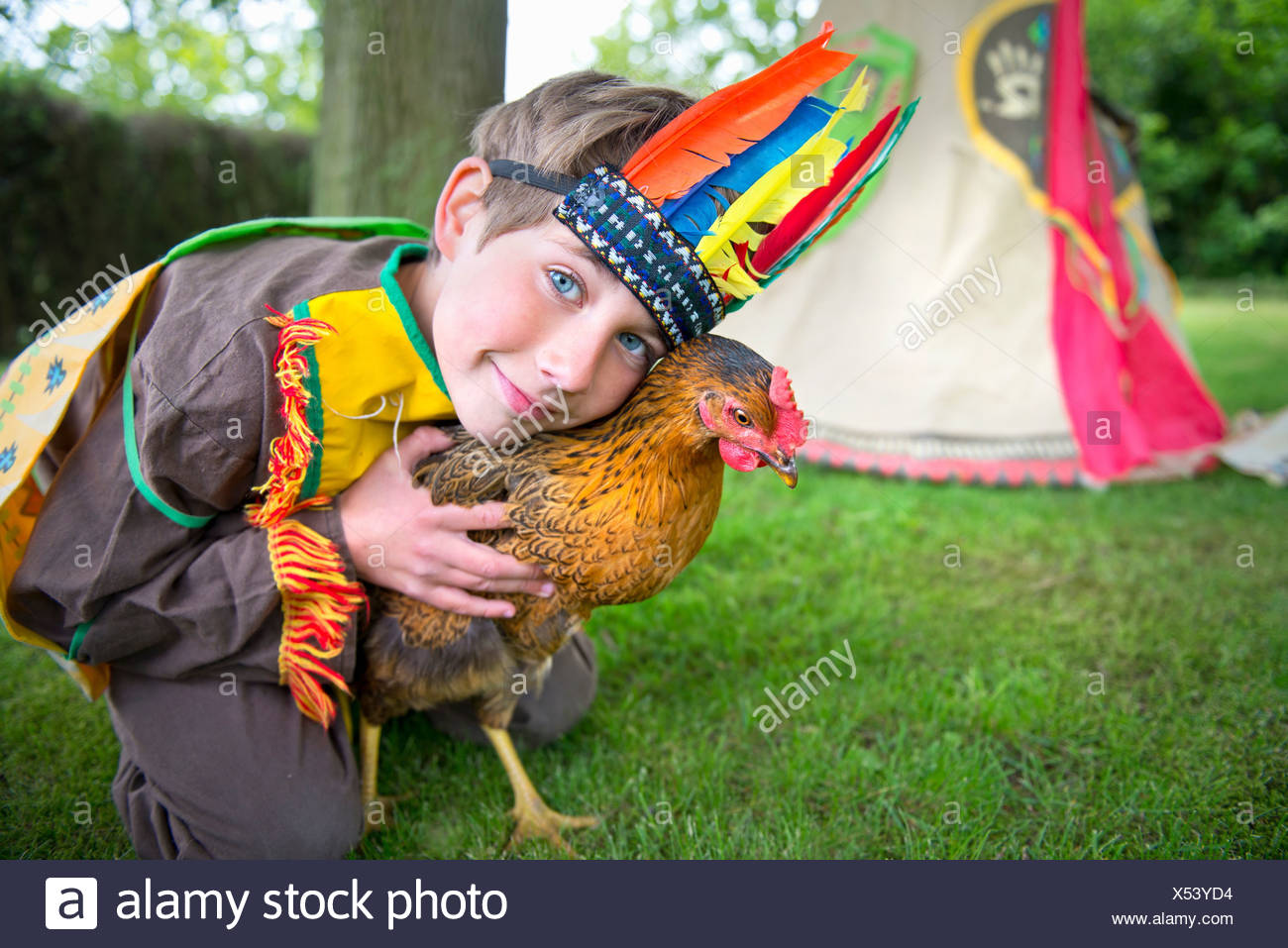 Boy dressed in Native American costume holding chicken, portrait - Stock Image