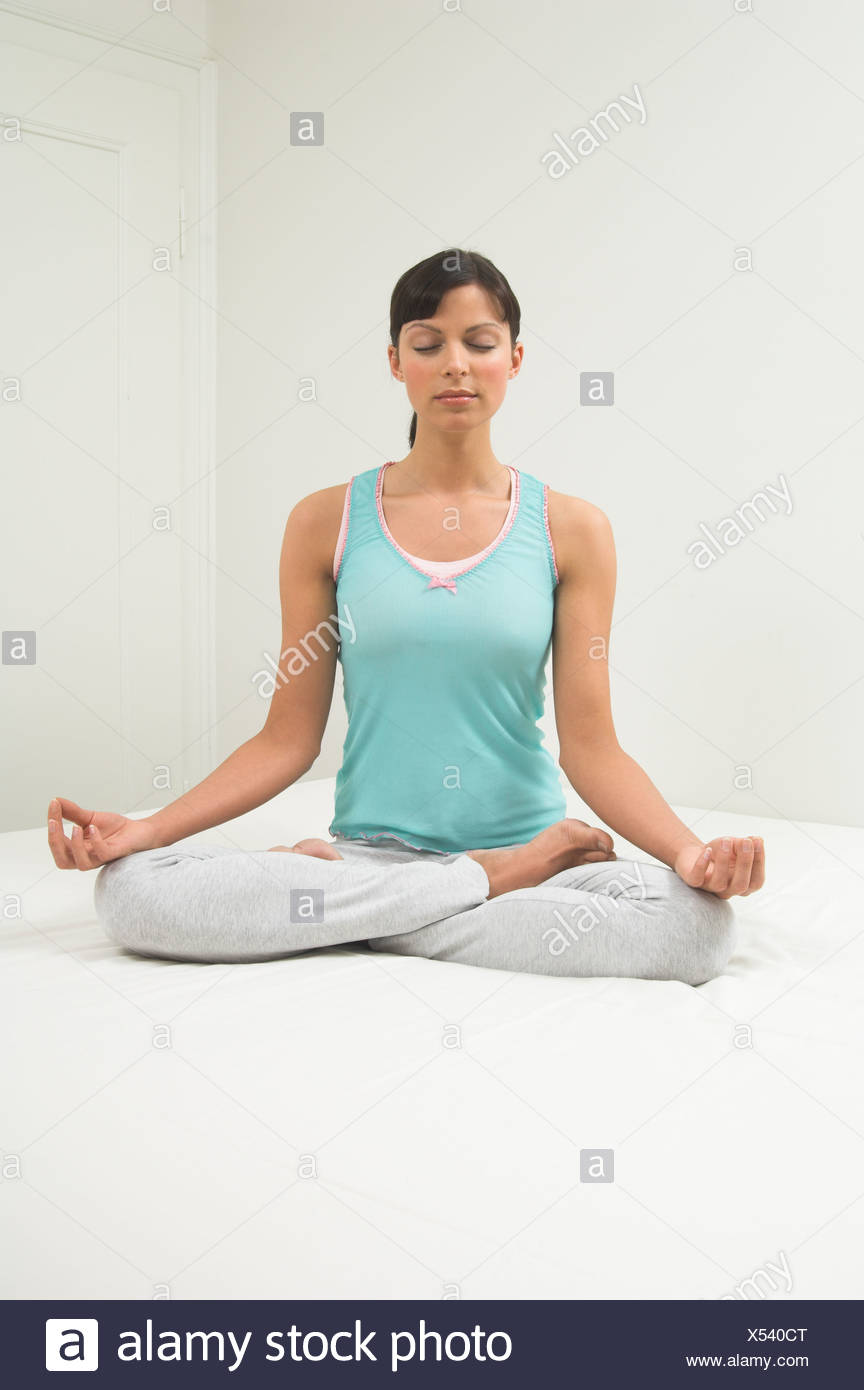 portrait of young woman sitting on bed doing yog in lotus position - Stock Image