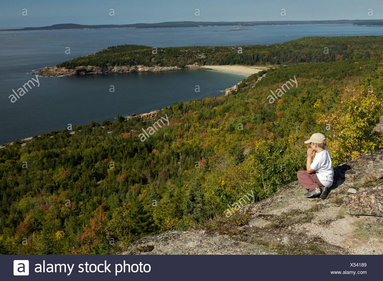 An elementar age boy enjoys the view from Gorham mountain. Stock Photo
