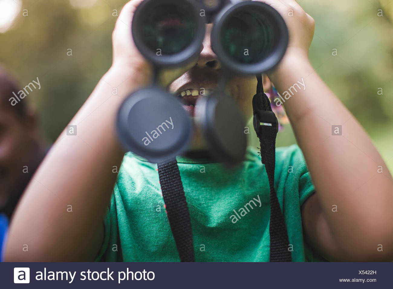 Close up of girl looking through binoculars in forest eco camp - Stock Image
