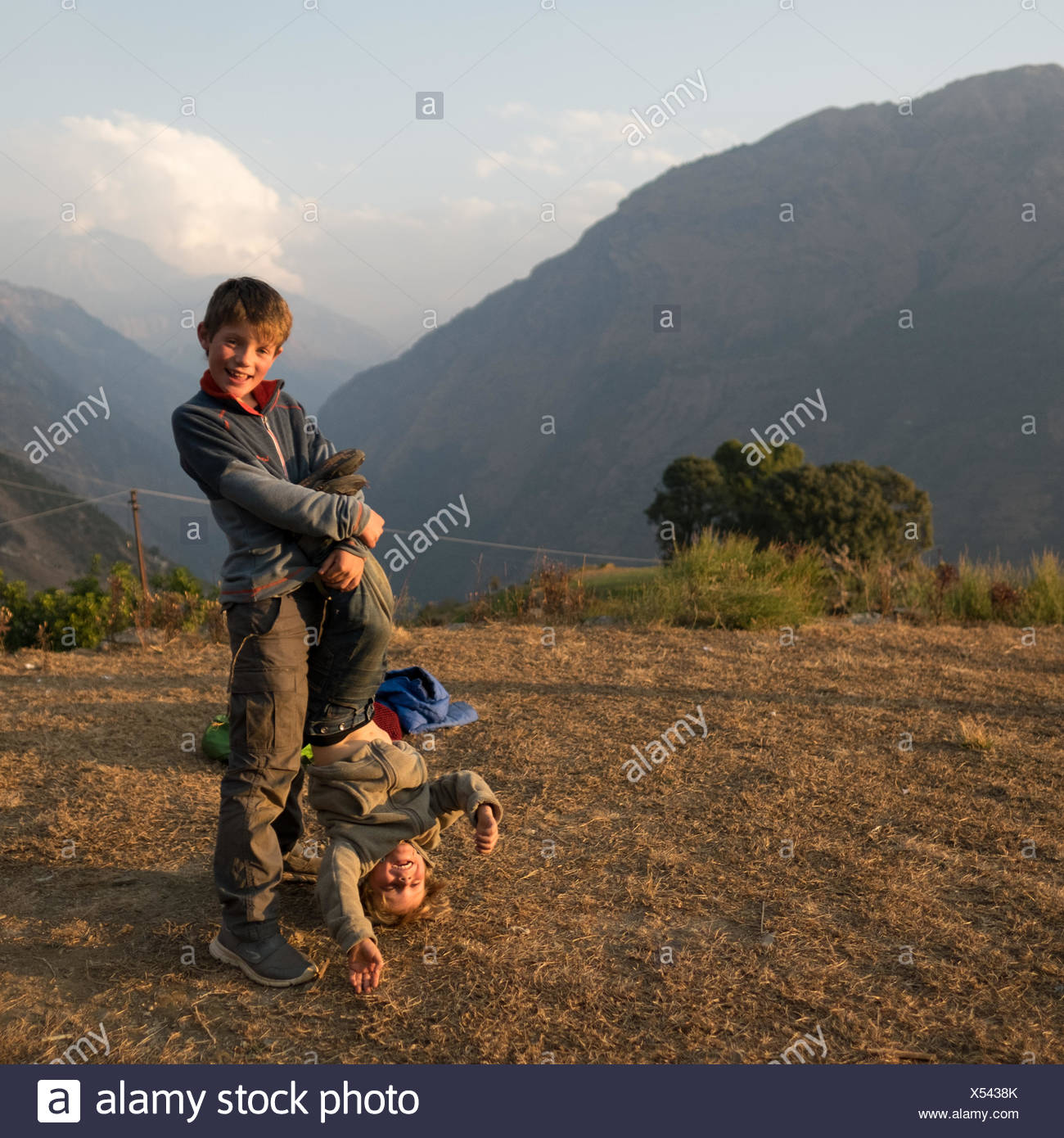 Older brother holds his younger brother upside down. - Stock Image