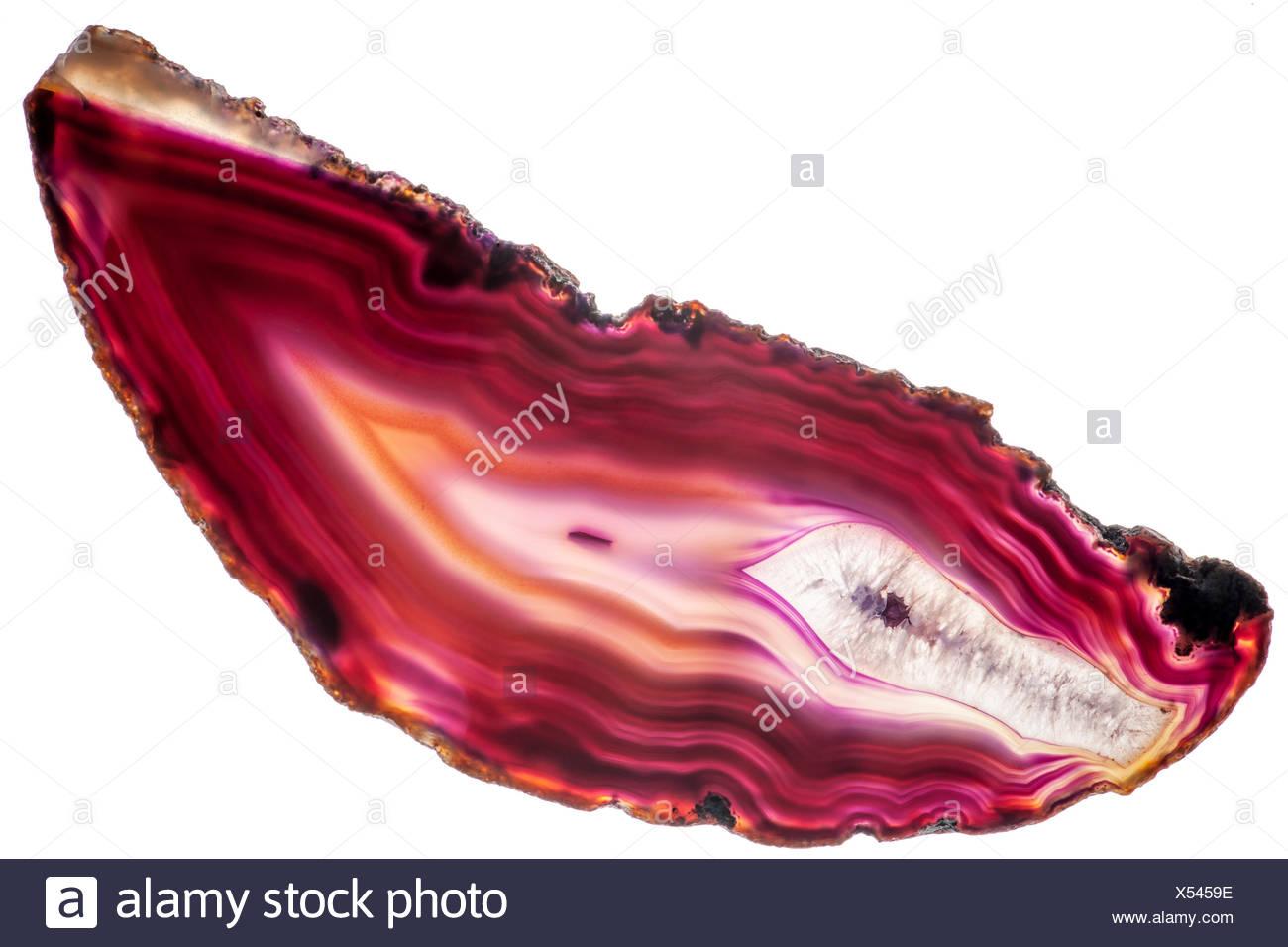 Ansicht einer länglich-flachen, polierten und transparenten Scheibe eines roten Achat mit pfeilförmigen Strukturen in violett mit krustigem Rand isoliert auf Weiß - Stock Image