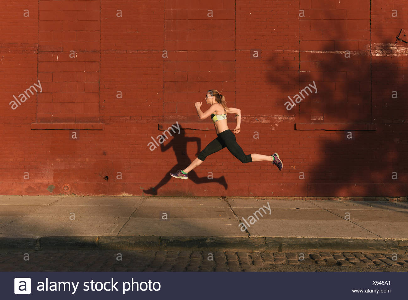 Young woman exercising outdoors, leaping through air, shadow beside her,  Brooklyn, New York, USA - Stock Image