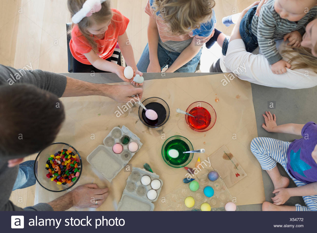 Overhead view family dipping Easter eggs food coloring - Stock Image