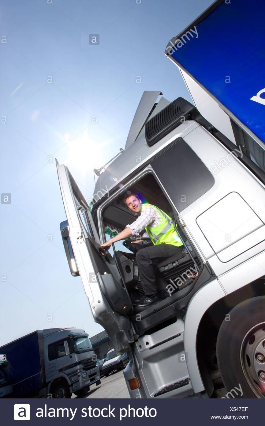 Truck driver closing door of semi-truck - Stock Image