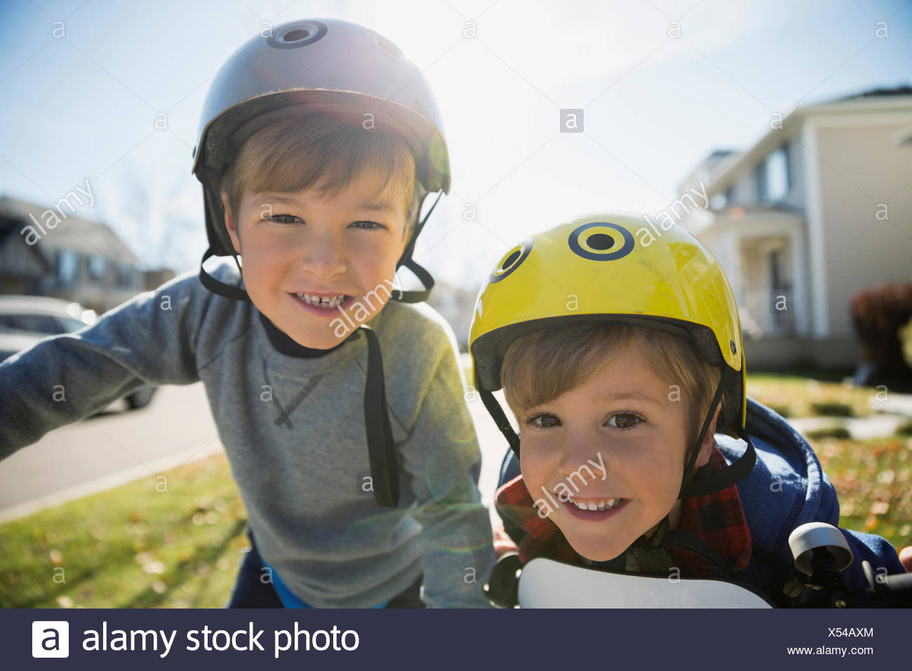 Portrait smiling brothers wearing helmets - Stock Image