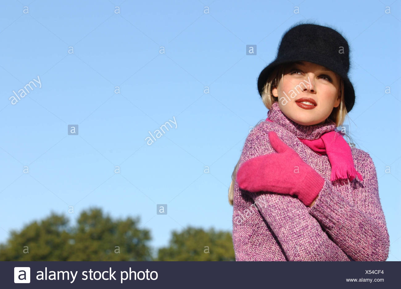 Female long blonde hair brown tones of make up wearing black angora hat purple roll neck jumper bright pink scarf and mittens - Stock Image
