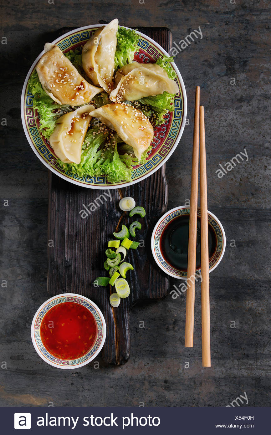 Gyozas potstickers on lettuce salad with sauces. Served in traditional china plate with chopsticks and spring onion on wood serving board over old met - Stock Image
