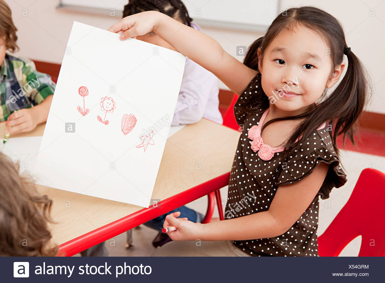 Girl with a crayon drawing - Stock Image