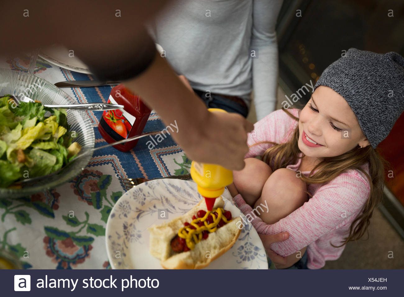 Girl watching brother squirt mustard on hot dog - Stock Image