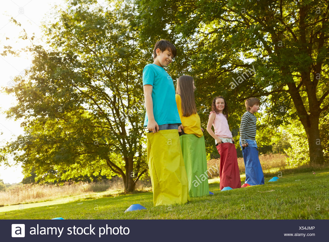 Girls and boys on start line for sack race in park Stock Photo