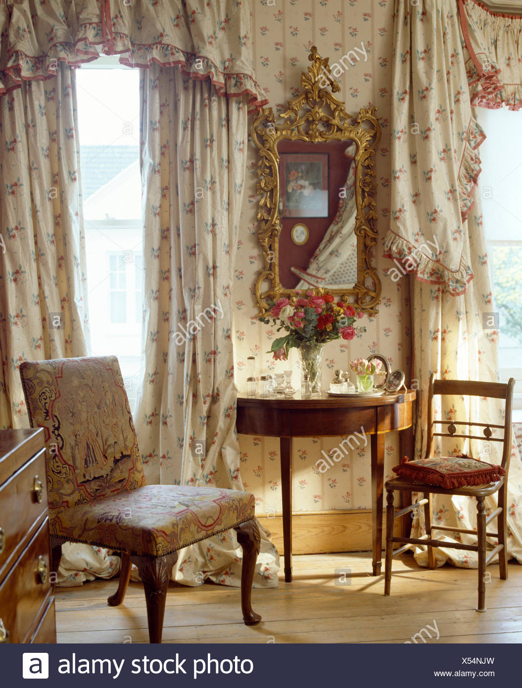 Floral curtains and pelmet on windows in bedroom with antique gilt ...