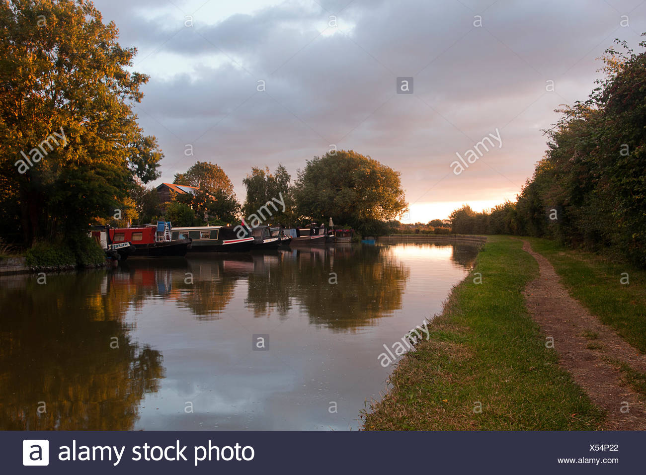 narrowboats and towpath along Cooks Wharf at sunset, Grand Union Canal Outer Aylesbury Ring, Cheddington, Buckinghamshire, England - Stock Image