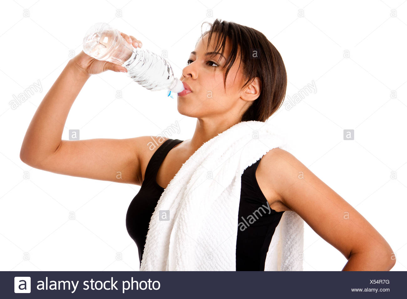 Beautiful attractive young sweaty woman drinking water after exercise workout, rehydrating thirst quenching, isolated. Stock Photo