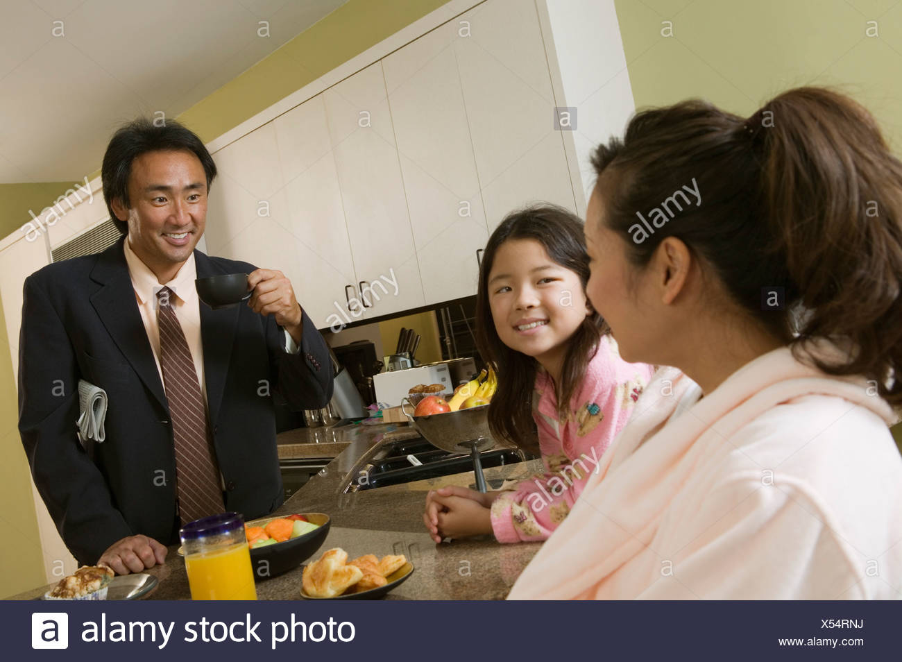 Family at breakfast table, father ready for work - Stock Image