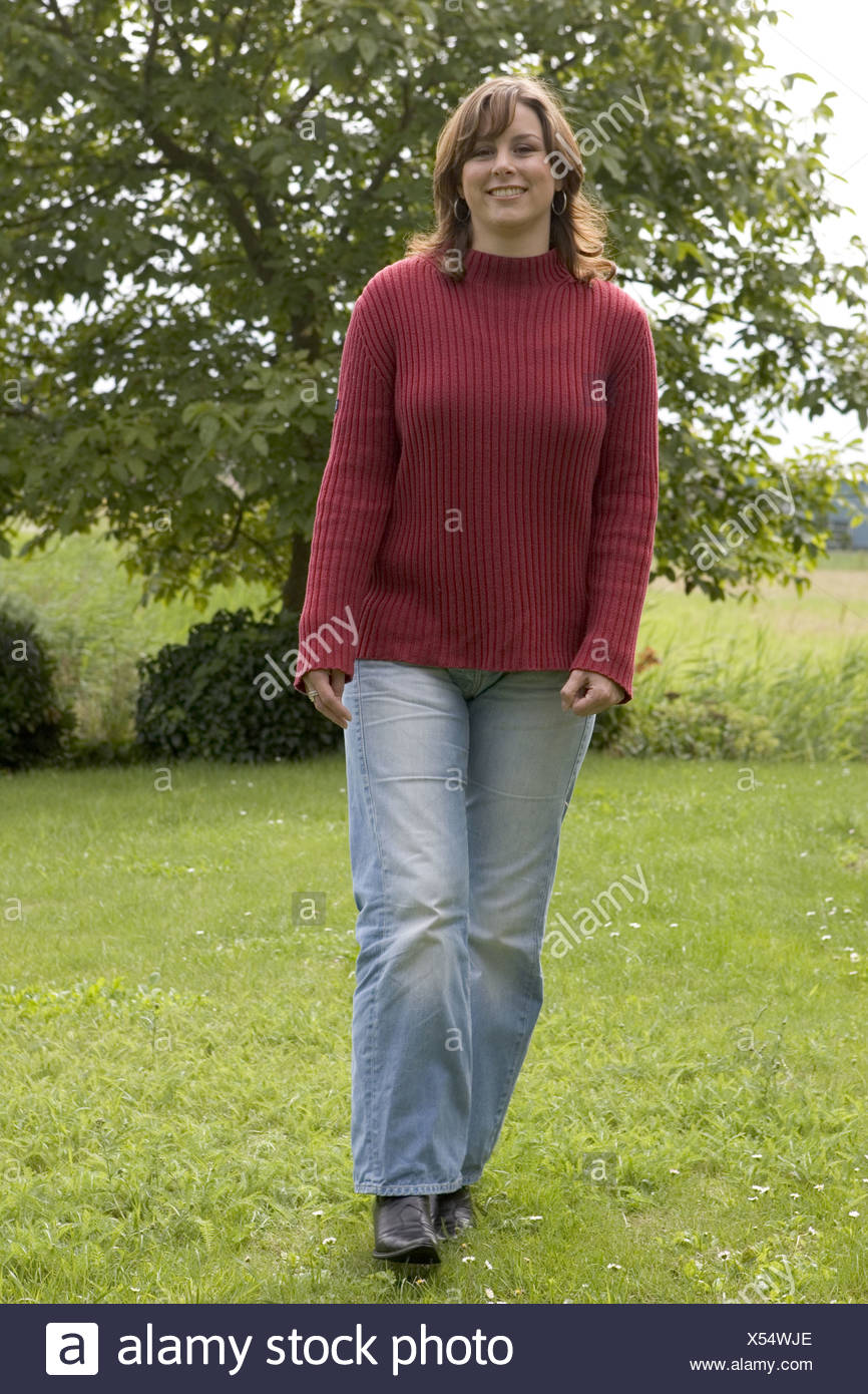 Happy young woman walking routine outside - Stock Image