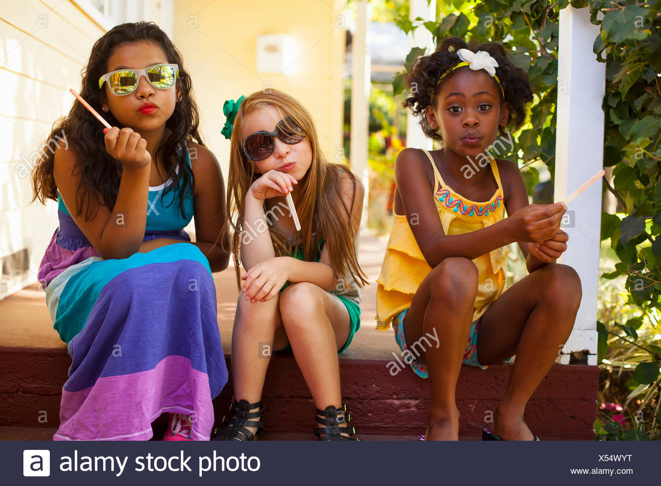 Three girls pulling faces on porch - Stock Image