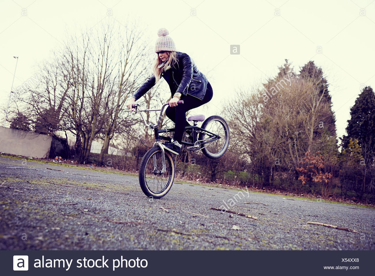 Female BMX rider doing BMX trick on wasteland - Stock Image