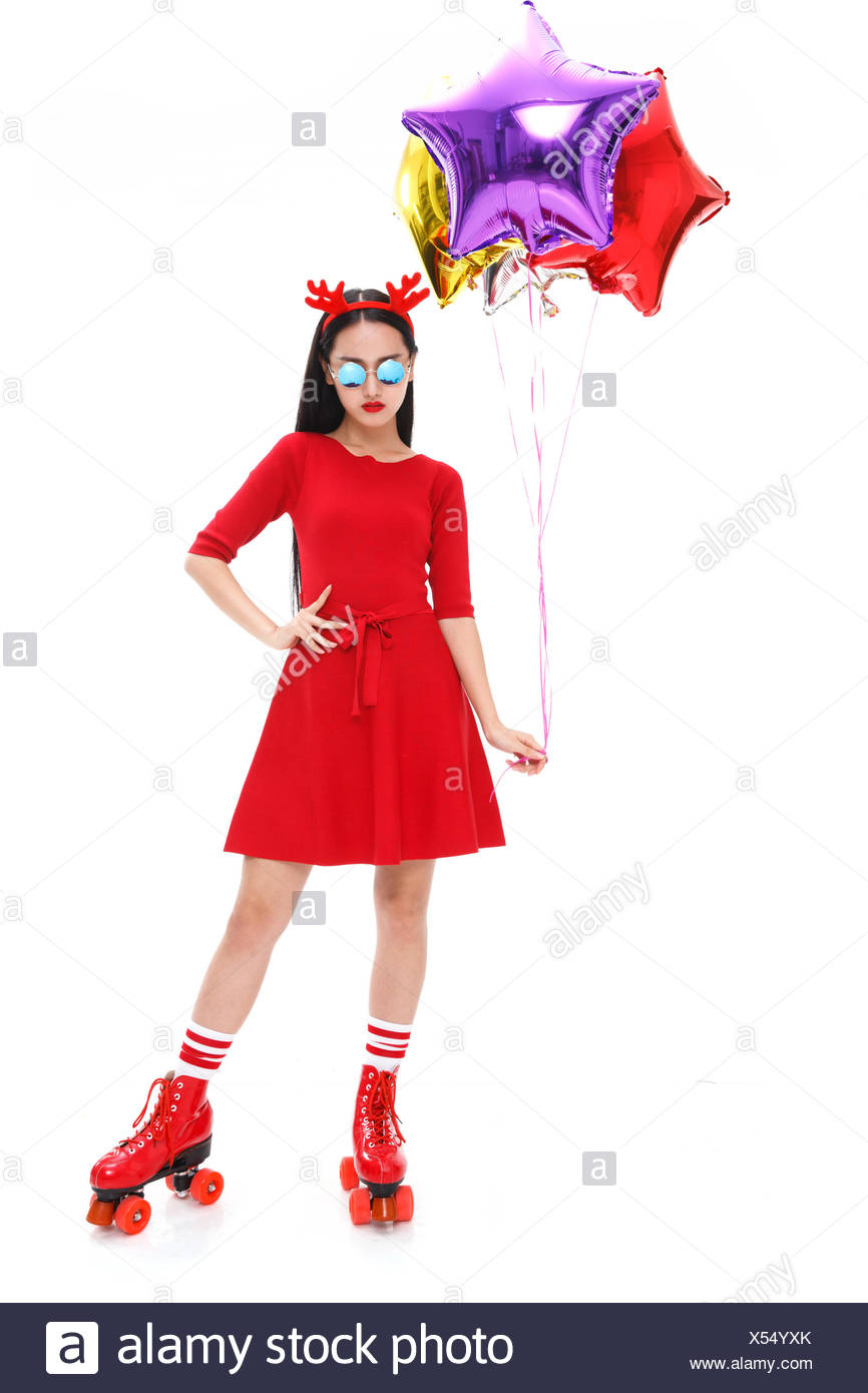 A young woman wearing skates with balloons - Stock Image