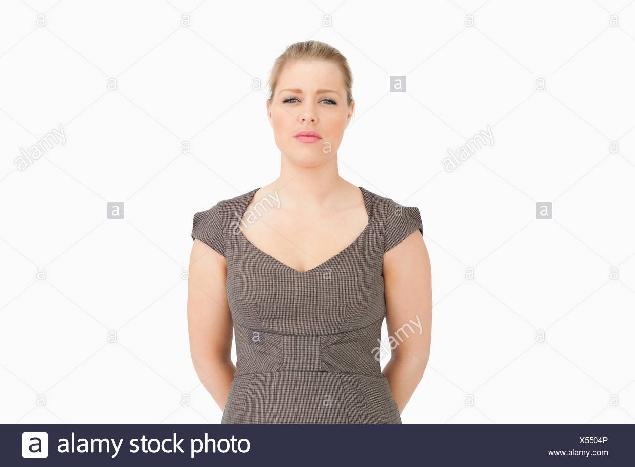 Woman standing with her arms behind her back - Stock Image
