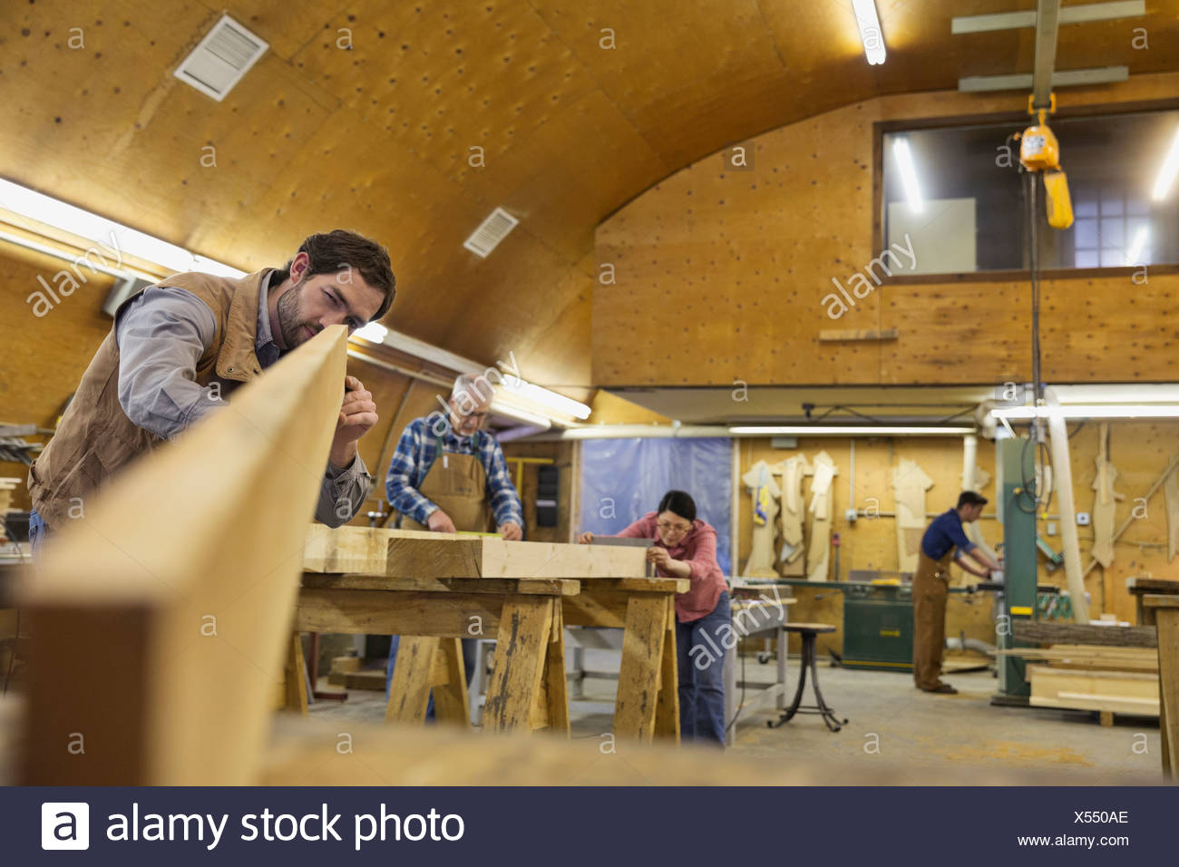Woodworker checking trueness of wood plank - Stock Image