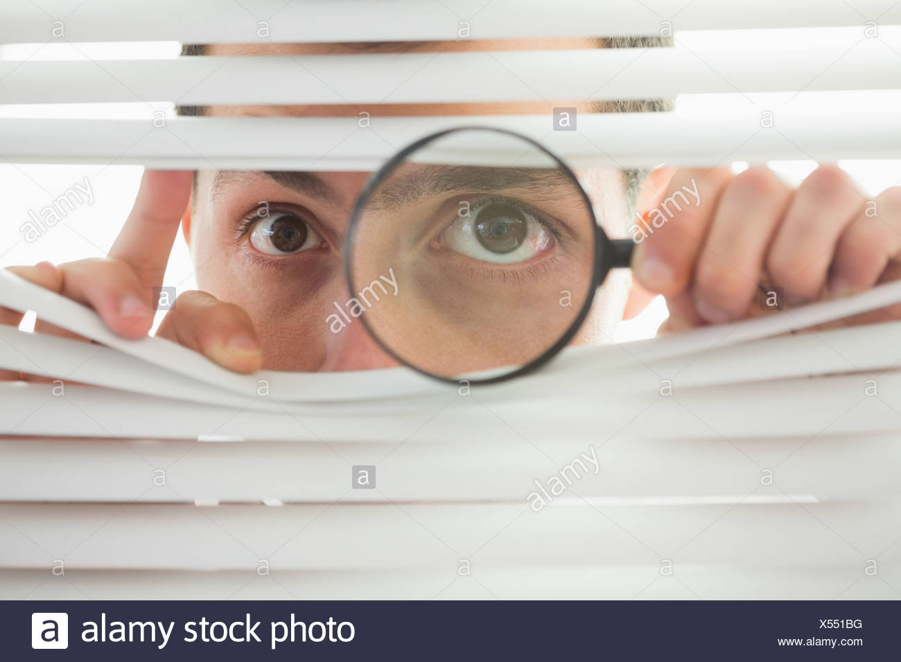Male eyes spying through roller blind with loupe - Stock Image