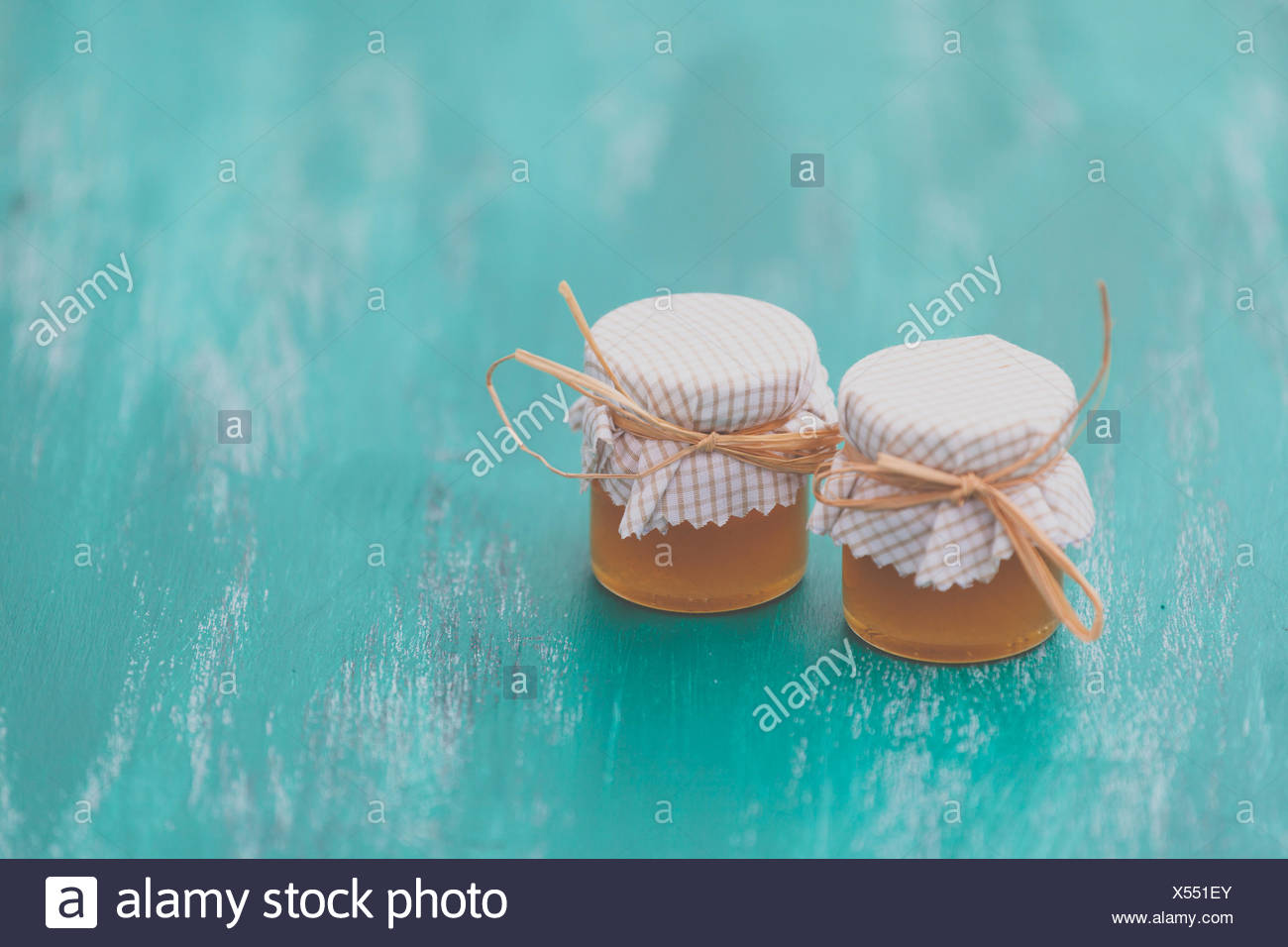 Close-Up Of Honey Jars Covered With Fabric On Table - Stock Image