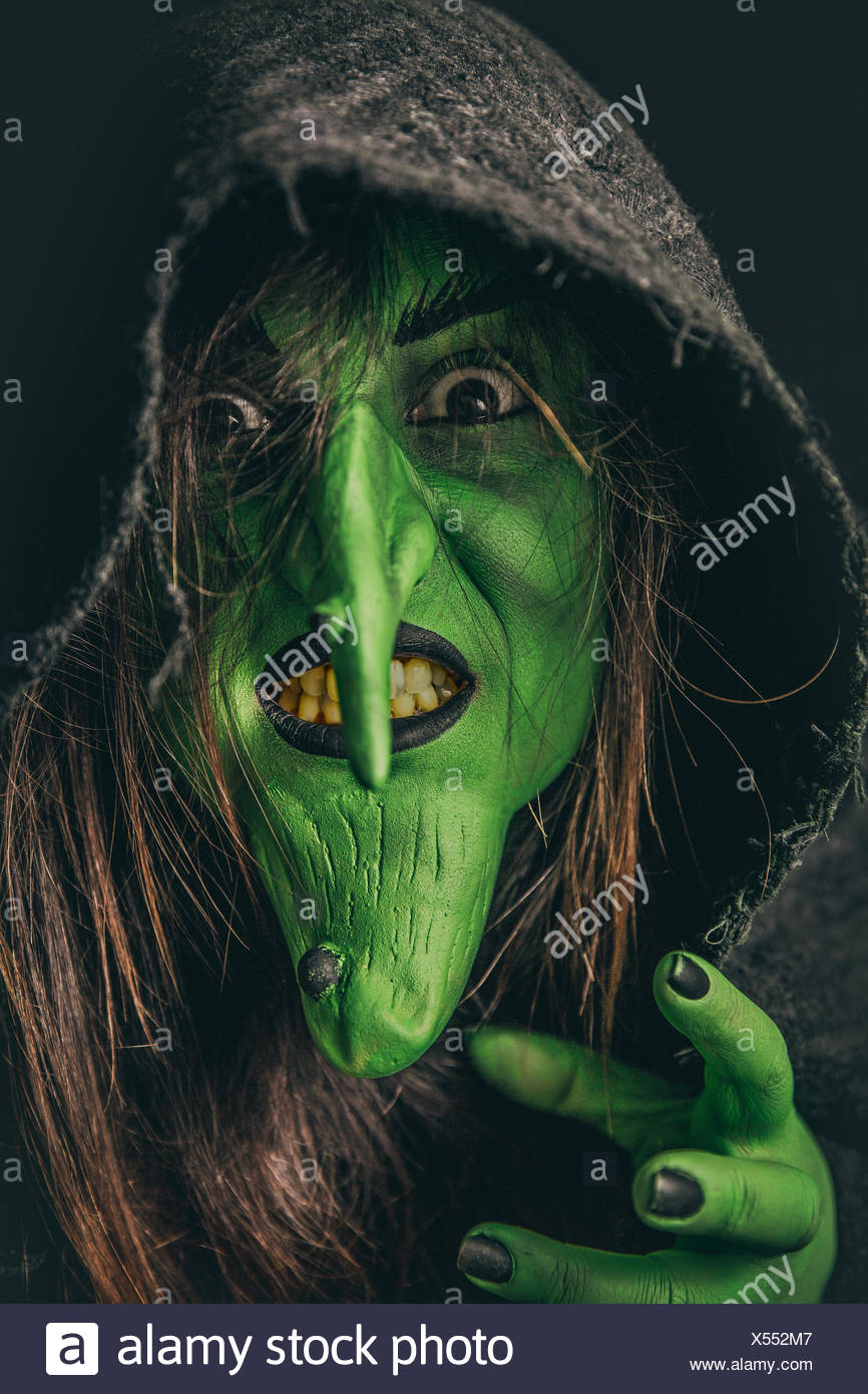 Evil witch casting a curse under her hood - Stock Image