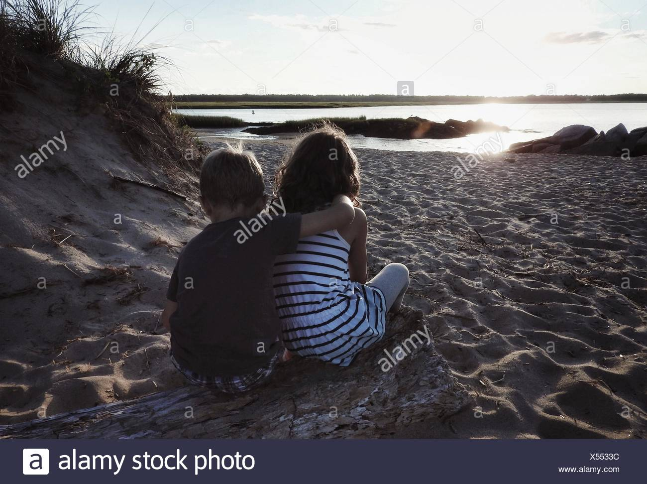 Rear View Of Brother With Arm Around Sister Relaxing On Sandy Beach - Stock Image
