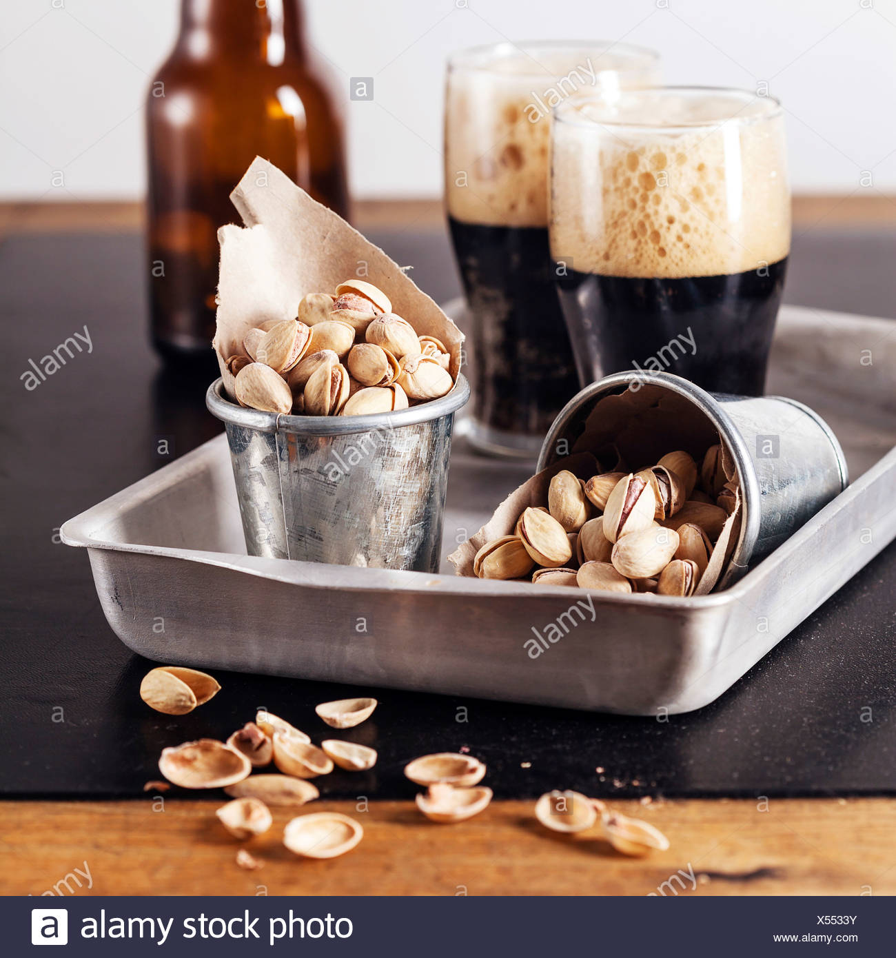 Dark beer and salted pistachios - Stock Image