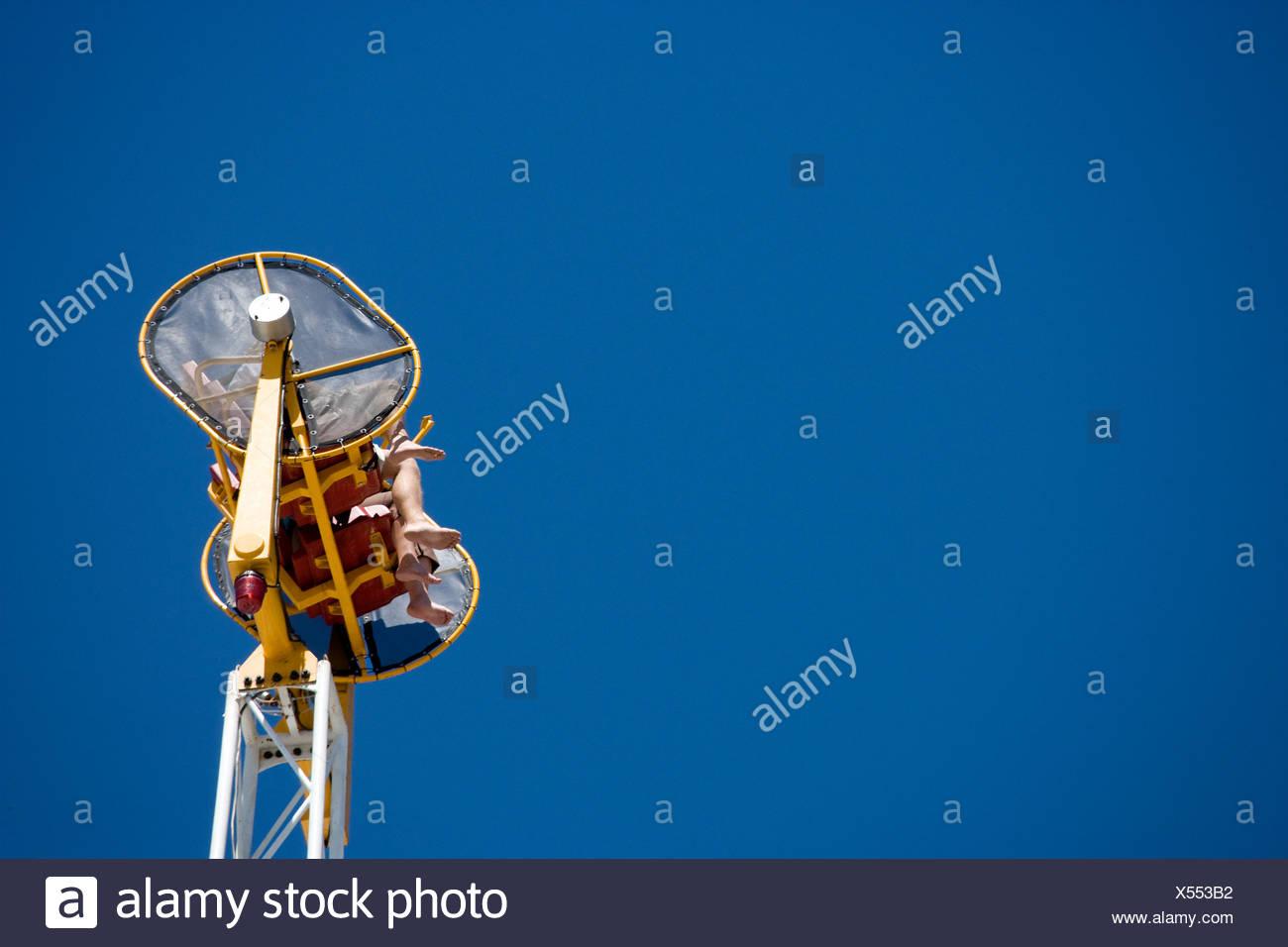 Feet dangle from an amusement park ride. - Stock Image