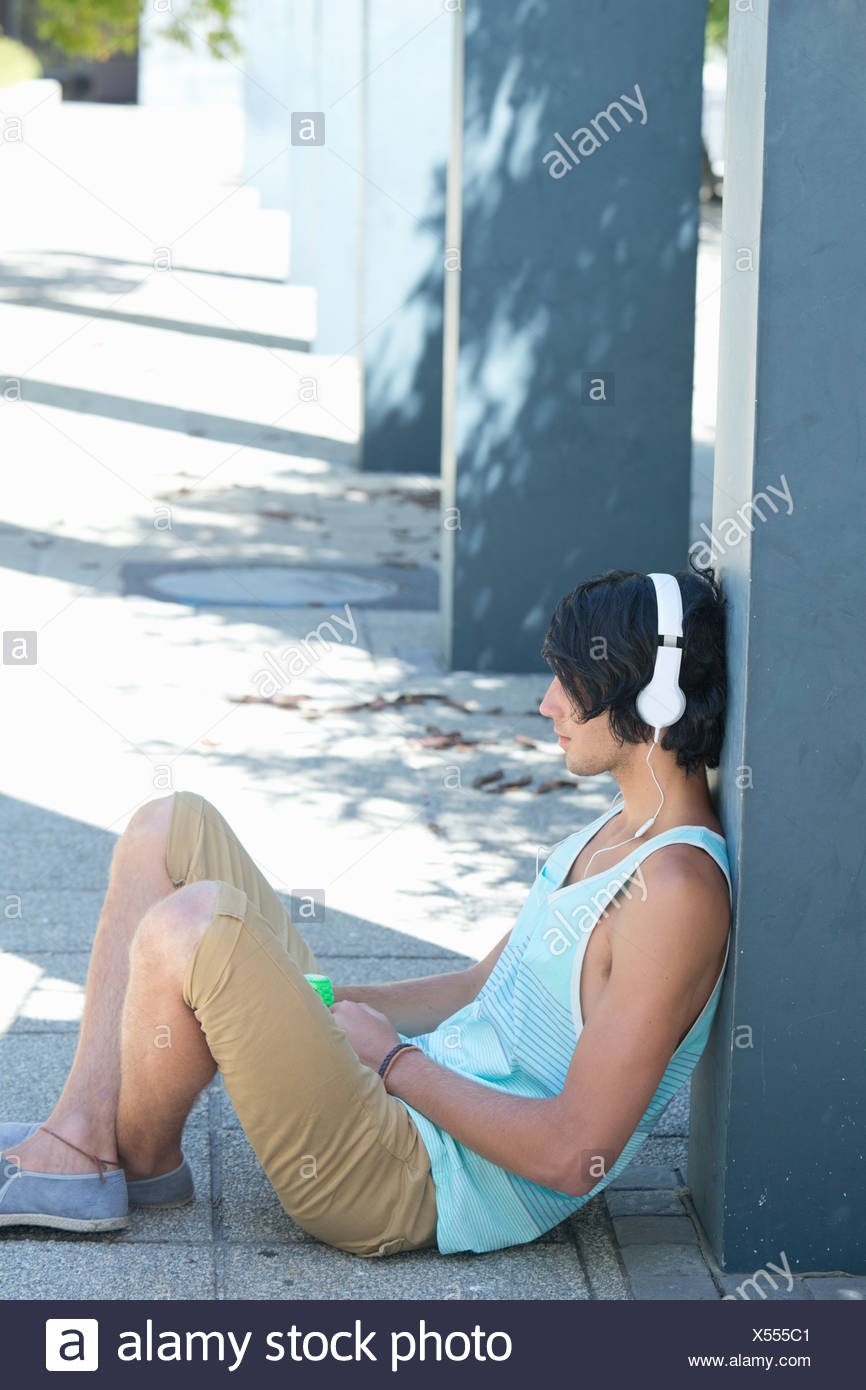 Young man wearing headphones and leaning against column - Stock Image