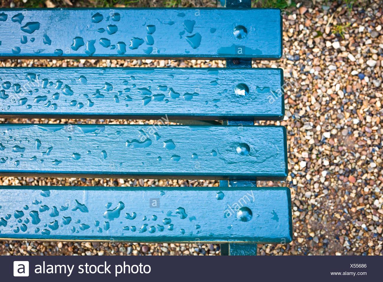 Rain drops on a blue park bench - Stock Image