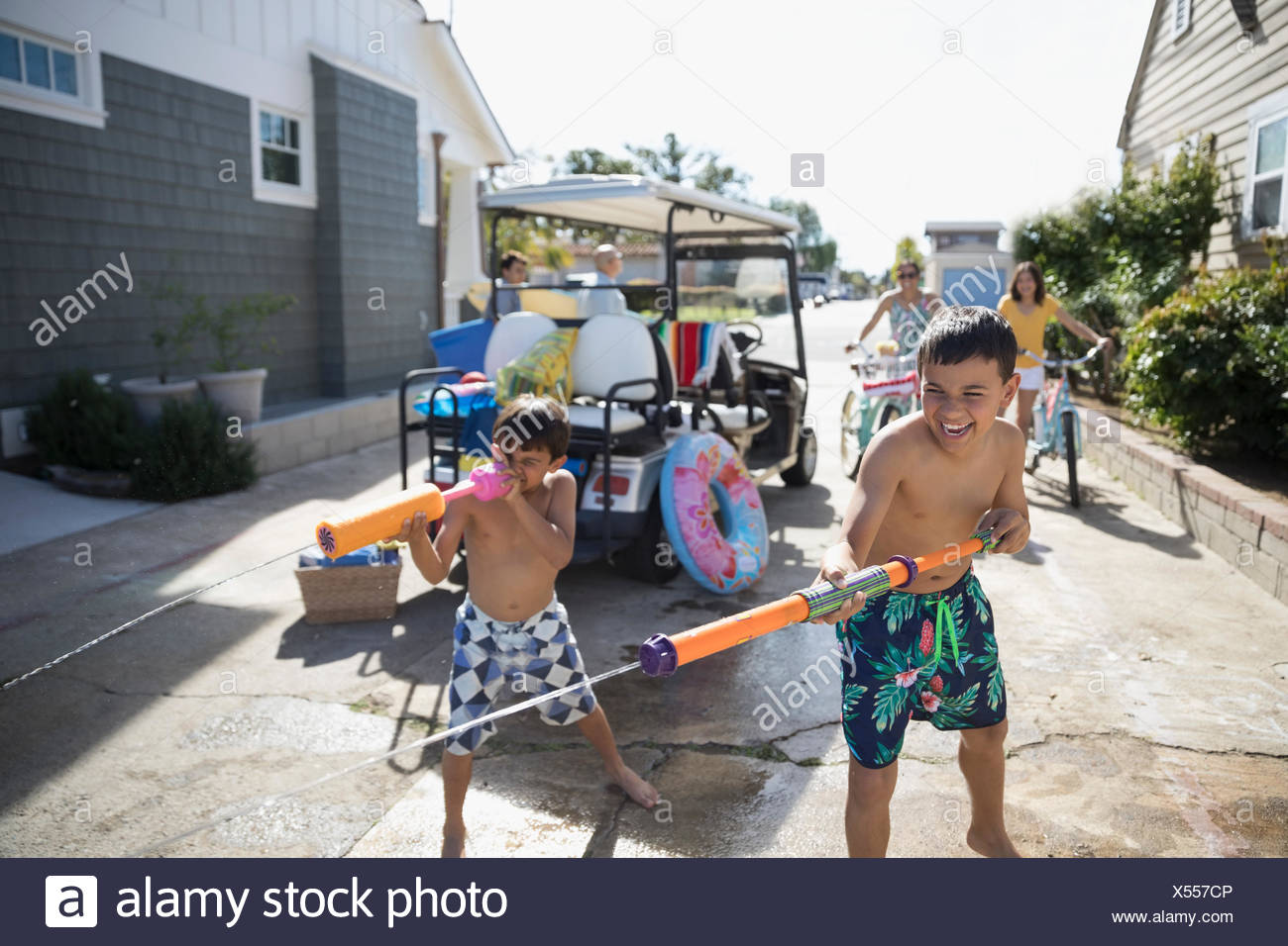 Brothers in swim trunks playing with squirt guns in summer driveway - Stock Image